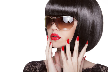 Fashion portrait of brunette woman in sunglasses showing red manicured polish nails. Professional makeup and hairstyle. Model isolated on white . Stock Photo - 24106333