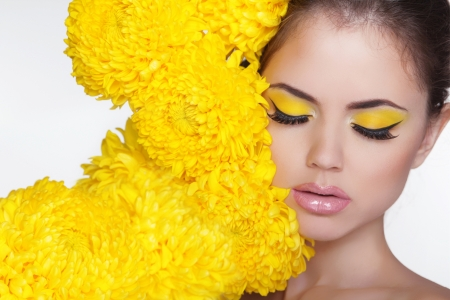Beautiful Spa Woman over chrysanthemum flowers. Eyes makeup. Beauty Portrait. Perfect Fresh Skin. Pure Beauty Model Girl. Beautiful Face.  스톡 콘텐츠