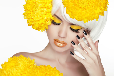 yellow: Beauty Blond Female Portrait with yellow flowers. Beautiful Spa Woman Touching her Face. Makeup and manicured nails. Perfect Fresh Skin. Isolated on white background