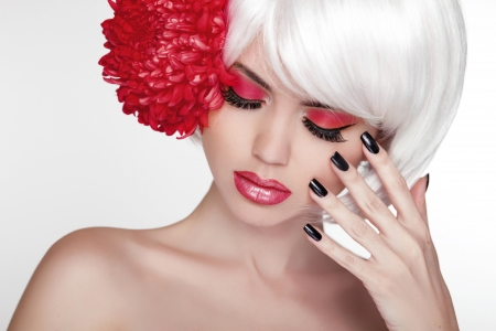 Beauty girl Portrait with red flower. Beautiful Spa Woman Touching her Face. Make up and manicured nails. Perfect Fresh Skin.