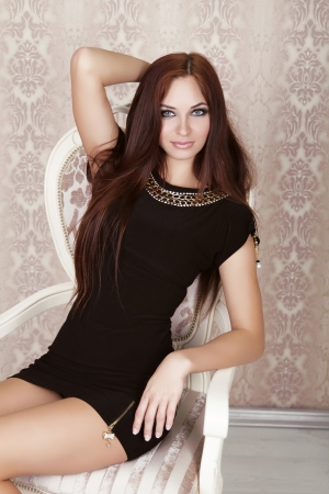 Fashion portrait of beautiful brunette woman in black dress sitting on moder chair photo