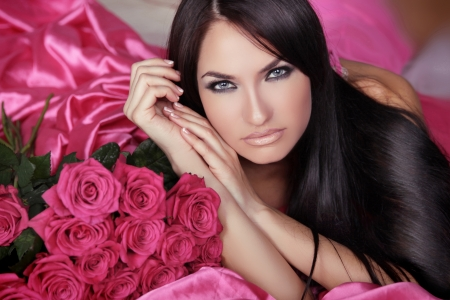 black hair blue eyes: Beauty portrait of brunette girl with pink Roses lying on the bed. Beautiful Woman with Blue Eyes and long black hair. Passion
