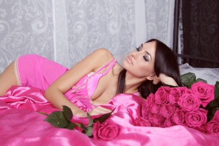 Beauty portrait of brunette girl with pink Roses lying on the bed. Valentines day Stock Photo - 24101612