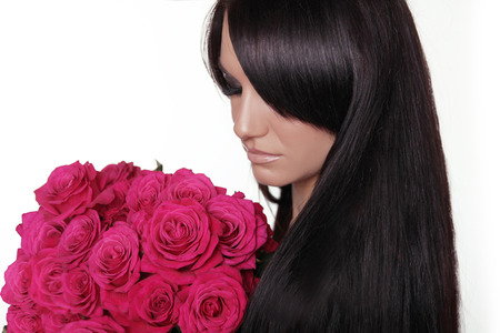 Healthy long hair. Brunette woman with fringe holding pink bouquet of roses isolated on white background. Hairstyle. Stock Photo - 24101411