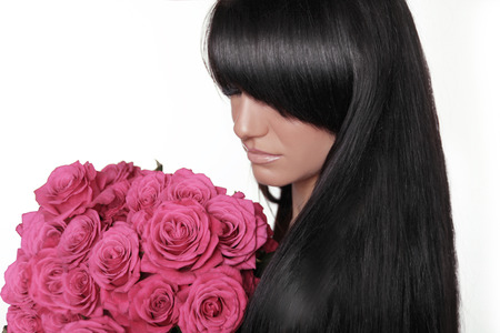 Brunette woman with fringe holding pink bouquet of roses isolated on white background. Long hair style. Hairstyle. photo