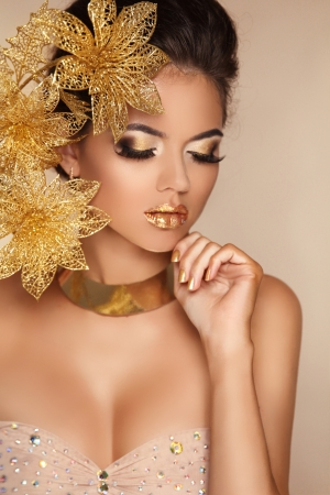 Glamour Makeup. Girl Face Close-up. Beauty Portrait Woman with golden flowers. Gold Jewelry. Hairstyle. Luxury photo