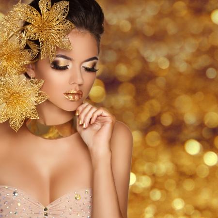 glitter makeup: Retrato de la muchacha de la belleza de la manera con las flores aisladas en el fondo de oro de las luces de bokeh. Maquillaje Glamour. Joyas de oro. Peinado. Foto de Lujo
