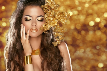 make a gift: Fashion Beauty Girl Isolated on golden bokeh lights Background. Glamour Makeup. Gold Jewelry. Hairstyle.  Stock Photo