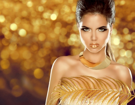 Fashion Beauty Girl Isolated on golden bokeh Background. Makeup. Gold Jewelry. Hairstyle. Vogue Style. 스톡 콘텐츠
