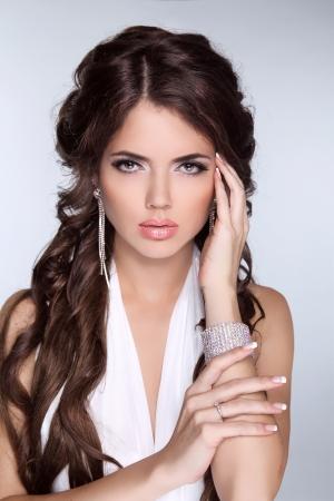 morena: Glamour Moda Mujer Retrato de la hermosa morena con el pelo largo aislado en el fondo gris. Accesorios de la joyería.
