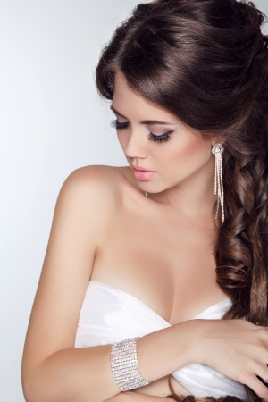 Beautiful woman with curly hair and evening make-up isolated on grey background. Jewelry and Beauty. Fashion photo  photo