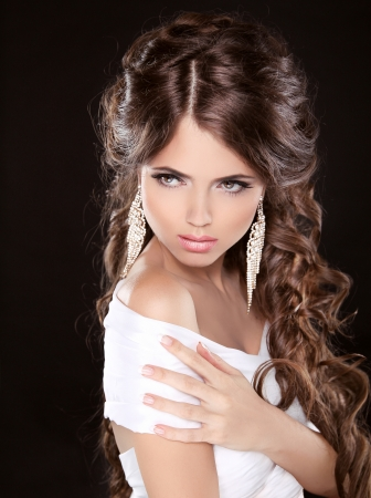 Beautiful woman with curly hair and evening make-up isolated on black background. Jewelry and Beauty. Fashion photo