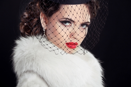 Beauty portrait of passionate elegant woman with hot red lips, wearing in white fur coat Isolated on black background. photo