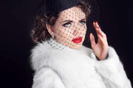 Winter Portrait of elegant retro woman wearing little hat with veil and white fur coat photo