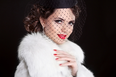 Fashion Portrait of elegant retro woman wearing little hat with veil and white fur coat photo