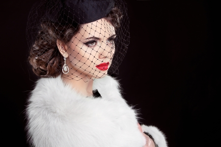 diamond jewellery: Fashion Brunette Model Portrait. Jewelry and Hairstyle. Elegant lady wearing in white fur coat Isolated on black background. Stock Photo