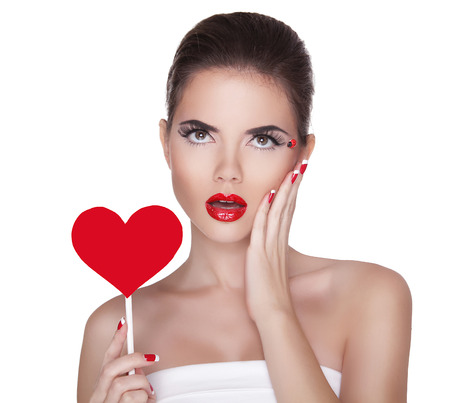 Beautiful surprised woman with glamour bright makeup holding red heart isolated on white background. Manicured nails and Red Lips. photo