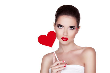 Beauty portrait of sexy cute girl with bright makeup holding red heart isolated on white background. Manicured nails and Red Lips. photo