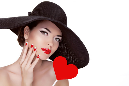 Valentines Day. Beautiful woman with heart in her hand wearing in elegant hat. Makeup. Manicured nails. Beauty portrait of attractive girl.