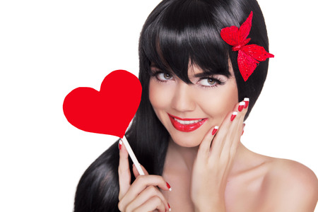 Beauty portrait of happy smiling girl with red lips holding red heart isolated on white background. Makeup and manicured nails. Valentines day. Studio photo
