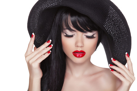 Beauty fashion sexy girl portrait in black hat. Red lips and polish manicured nails. Attractive cute model with long hair isolated on white background.