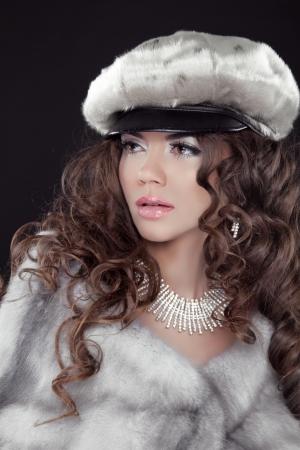 kepi: Fashion woman in luxury fur coat with diamond necklace posing in kepi isolated on black background Stock Photo