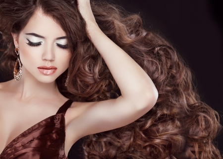 Glamour Fashion Woman Portrait with professional makeup and curly hair styling.