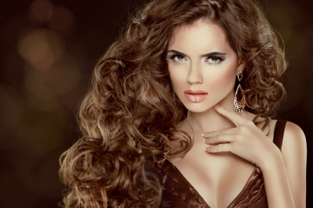 Beauty Model Girl with luxurious wavy long hair isolated on dark background photo