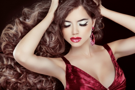 red lip: Beautiful brunette with long wavy hair and sexy red lips posing isolated on black background