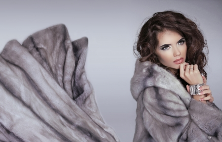 Mink fur coat. Winter girl. Beautiful brunette woman isolated on grey background. Glamour Fashion Woman Portrait. photo
