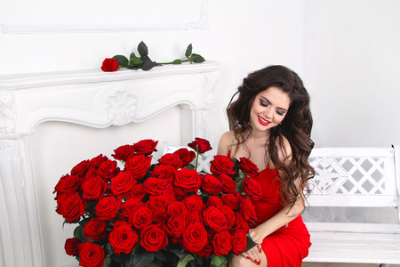 Beautiful smiling brunette woman with red roses bouquet, valentines day. Luxury life. photo