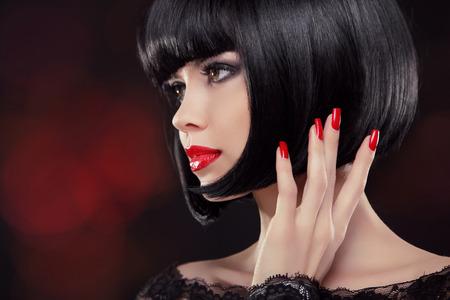 Brunette vrouw portret. Zwart kort kapsel. Gemanicuurde nagels en rode lippen. Fashion Beauty Photo
