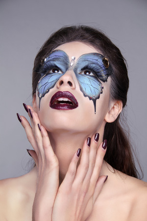 Face art portrait. Fashion model woman with painting butterfly over her Eyes. Stock Photo - 25663088