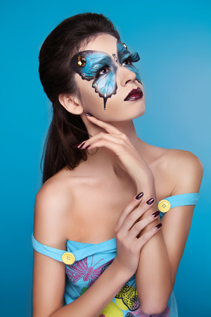 Makeup. Fashion face art portrait. Beautiful model girl posing isolated on blue . Stock Photo - 25663105