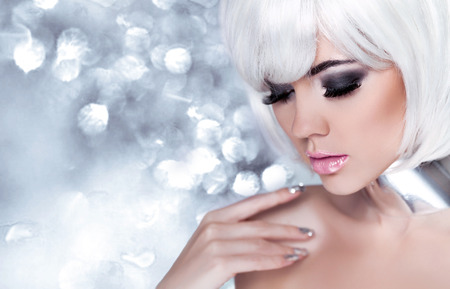 Fashion Blond Girl. Beauty Portrait Woman. Holiday Make-up. Snow Queen High Fashion Portrait over Blue bokeh Background. 스톡 콘텐츠