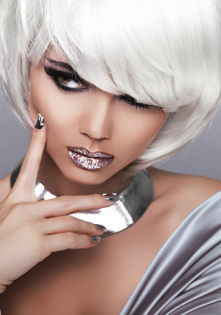 Fashion Blond Girl. Beauty Portrait Woman. White Short Hair. Sexy lips. Isolated on Grey Background. Face Close-up. Manicured nails. Hairstyle. Fringe. Vogue Style. photo