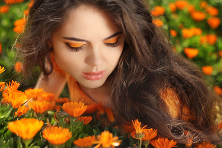 Beauty Girl over marigold flowers field photo