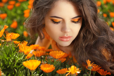 emotional freedom: Beautiful Teenage Model girl over marigold flowers field Stock Photo