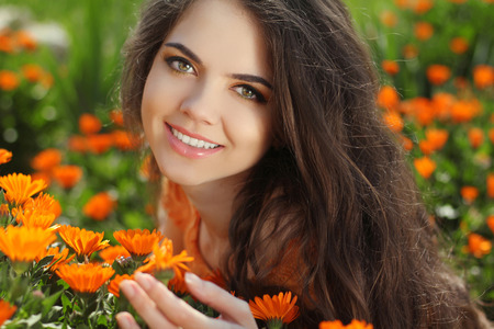 Beautiful Romantic Brunette female Over marigold flowers field photo