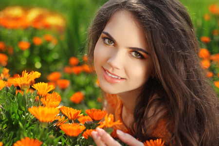 emotional freedom: Beautiful Romantic Brunette female Outdoors portrait Over marigold flowers field