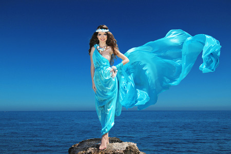 Fashion happy model woman with blowing dress over blue sky, outdoors photo