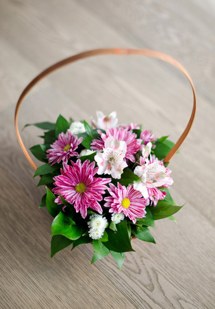 Beautiful bouquet of spring flowers in basket isolated on parquet floor photo