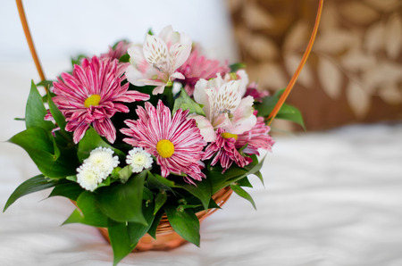 Beautiful bouquet of colorful flowers in basket against the bed sheet background photo