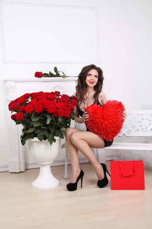 Happy smiling beautiful woman holding red heart over bouquet of roses and shopping gift. Valentine day love concept photo