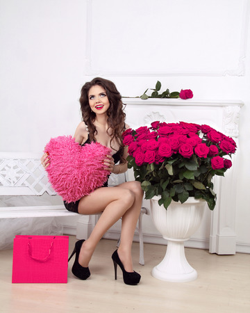 Happy smiling beautiful girl holding heart over pink bouquet of roses and shopping gift. Valentine day love concept. photo