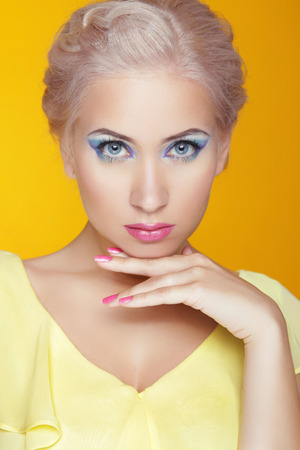 Beauty model portrait. Makeup. Attractive young woman isolated on yellow background photo