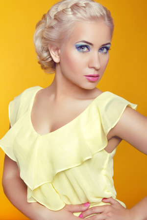 Blond young woman posing over yellow background photo