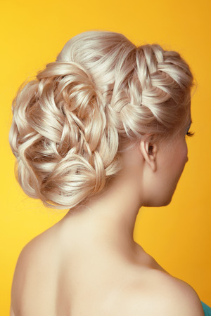 plait: Hairstyle. Beauty Blond girl bride with curly hair styling over yellow background