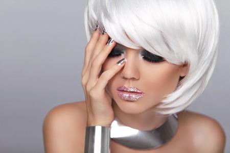 Fashion Blond girl. Makeup. Manicured nails. Beauty Portrait Woman isolated on gray background. . White Short Hair.  Fringe. Vogue Style. photo
