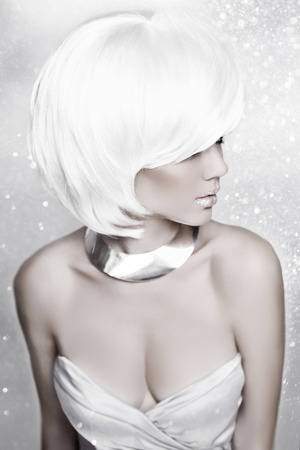 Winter Beauty Blond Woman. White Short Hair. Hairstyle. Holiday Make-up. Snow Queen High Fashion Portrait over Snow Background. photo